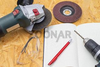 Winkelschleifer mit Bohrmaschine und Notizbuch