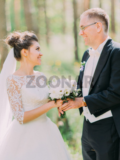 Side view of the cheerful newlyweds holding the wedding bouquet of the white peonies. Forest location.