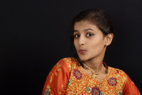 Portrait of a happy young Indian girl pursing her lips on black background.