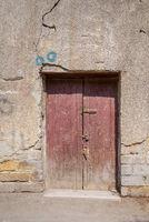 Broken wooden door on grunge stone bricks wall in abandoned street
