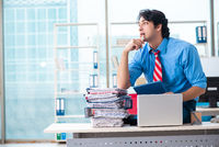 Handsome businessman unhappy with excessive work in the office