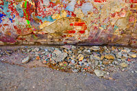 Damaged wall with building garbage beneath