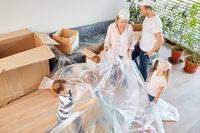 Eltern und Kinder als Heimwerker mit Schutzfolie