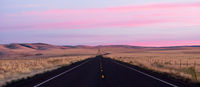 Flat Two Lane Blacktop Highway Heads into the Pink Sunset