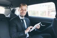 Executive businessman sitting at the back of car using a digital tablet