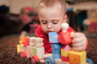 Little boy playing with a colourful wooden toy train