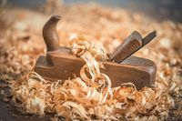 Old wooden hand plane for woodworking with wood shavings.