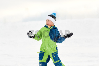 happy boy playing and throwing snowball in winter