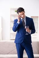 Businessman drinking wine sitting at home