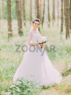 The walk of the wonderful happy bride along the green forest.