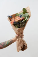Female hand shows bouquet with rose flowers on gray background. Gift for Mother or Woman's Day.