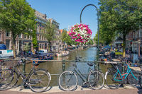 Bridge over canal with bicycles and flowers, Amsterdam, the Nethelands