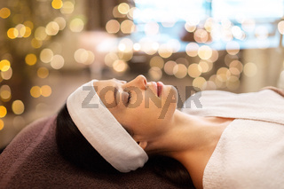 young woman with headband lying in spa parlor