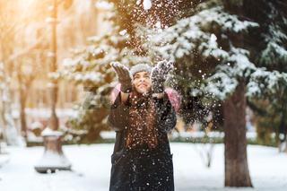 The girl throws snow up in the city.