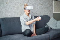 Young woman watching videos or playing with VR glasses on head