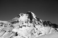 Black and white view on high snowy mountain at winter