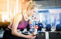 Frau gibt Bewertung am Smartphone im Fitnesscenter