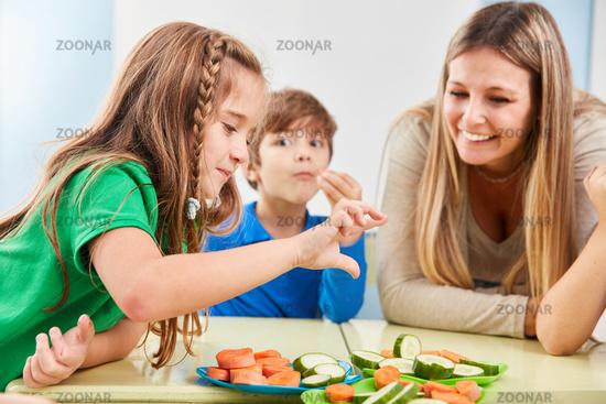 Kinder in der Grundschule essen Gemüse