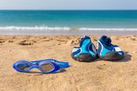 Swimming goggles and water shoes on beach at sea