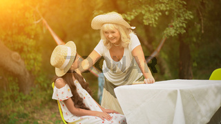 Grandmother And Granddaughter Are At The Table In The Garden