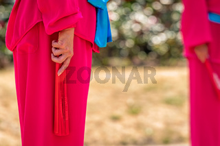 Woman holding red fan during Tai Chi exercises