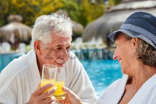 Glückliches Senioren Paar am Pool im Urlaub