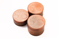 Three piles of five cents euro coins on white background