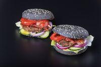 Nahaufnahme eines schwarzen Hamburgers auf schwarzem Schiefer
