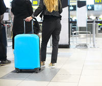 Young woman with luggage at airport check in