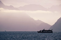 Boat on Swiss alke Luzern with mountain cliffs background silhouette view