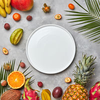 Palm leaves, empty white plate and a set of different tropical fruits mango, passion fruit,banana, coconut, physalis, pineapple on a gray concrete background with space for text. Flat lay