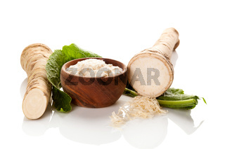 Fresh and grated horseradish in wooden bowl.