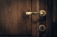 An old wooden door with golden handle sorrounded by black vignette