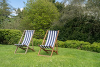 Two typical english deckchairs on lawn in garden