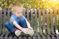 Young Boy Sitting On A Bench Putting On His Shoes At The Park