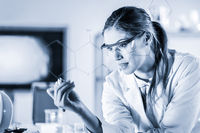 Portrait of a confident female researcher in life science laboratory writing structural chemical formula on a glass board.