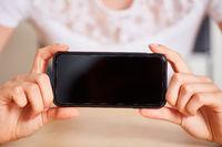 Hände zeigen leeren Bildschirm vom Smartphone