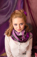 A young girl in a purple scarf looking at the camera