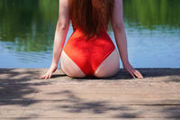 unrecognizable woman wearing red swimsuit sitting on wooden pier