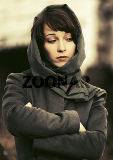 Sad young fashion woman in classic coat and headscarf walking outdoor