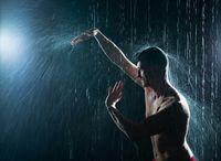 Shirtless man exercising under the rain in profile
