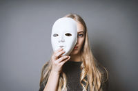 teen girl hiding face behind mask
