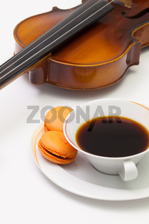 Old violin, cup of coffee and traditional french colorful macarons
