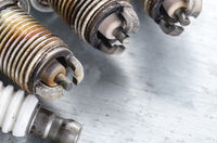 New and used spark plugs for internal combustion engine on metal background. Space for text
