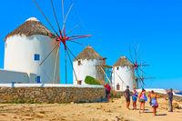 Tourists taking photos next to old windmills