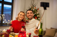 couple taking picture by selfie stick at christmas