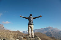 an applause of a young woman backpacker on top of a sprawling upward mountain peak. Freedom and victory against the background of mountains and blue sky