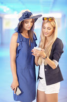 Two pretty young women look into the smartphone and talk