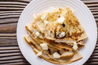 Flat lay of French crepes with butter and honey in ceramic dish on wooden kitchen table
