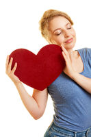 Junge Frau hält rotes Herz und träumt von Liebe